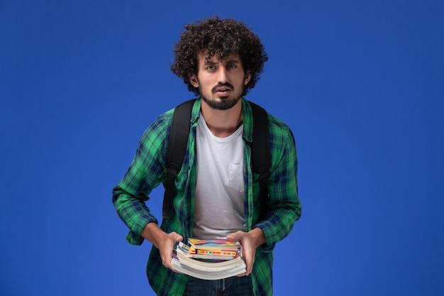 파란색 벽에 카피 북 및 파일을 들고 검은 배낭과 녹색 체크 무늬 셔츠에 남성 학생의 전면보기