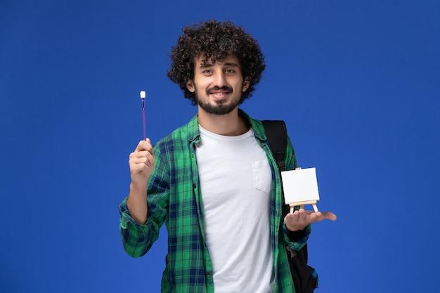 파란색 벽에 술과 이젤을 들고 검은 배낭과 녹색 체크 무늬 셔츠에 남성 학생의 전면보기