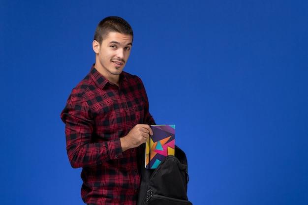 青い壁に彼のバックパックと法帖を保持している赤い市松模様のシャツを着た男子学生の正面図