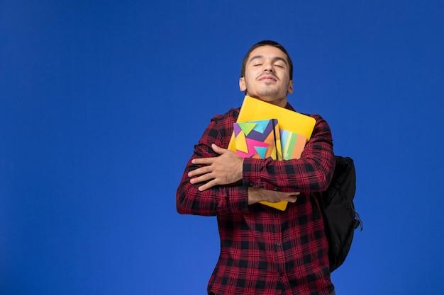 水色の壁にコピーブックとファイルを保持しているバックパックと赤い市松模様のシャツの男子学生の正面図