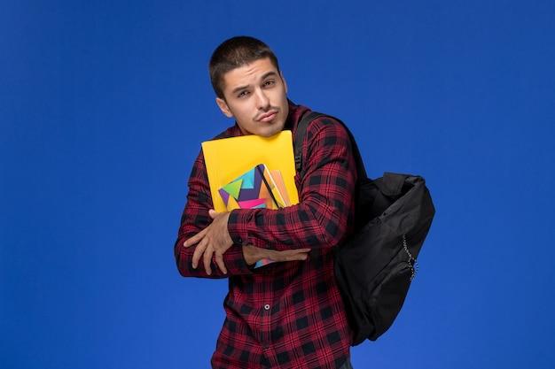 コピーブックと青い壁に電話でファイルを保持しているバックパックと赤い市松模様のシャツの男子学生の正面図