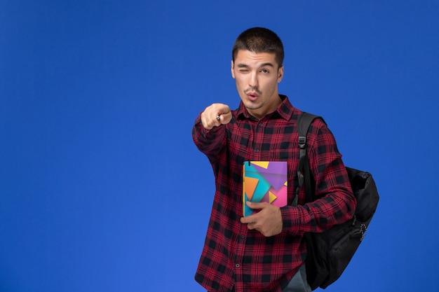水色の壁にウィンクするコピーブックを保持しているバックパックと赤い市松模様のシャツの男子学生の正面図