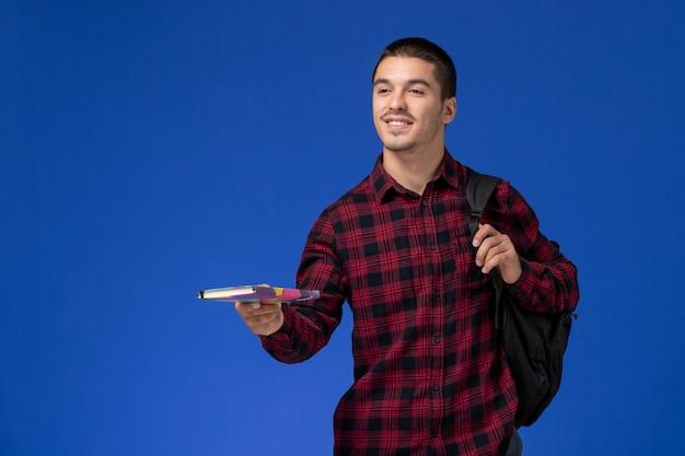 水色の壁に笑みを浮かべてコピーブックを保持しているバックパックと赤い市松模様のシャツの男子学生の正面図