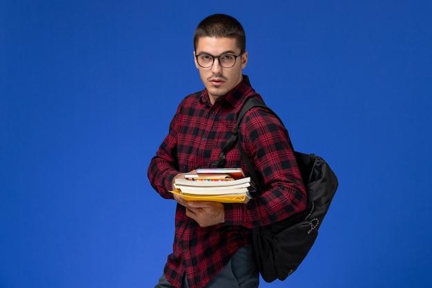 水色の壁にコピーブックを保持しているバックパックと赤い市松模様のシャツの男子学生の正面図