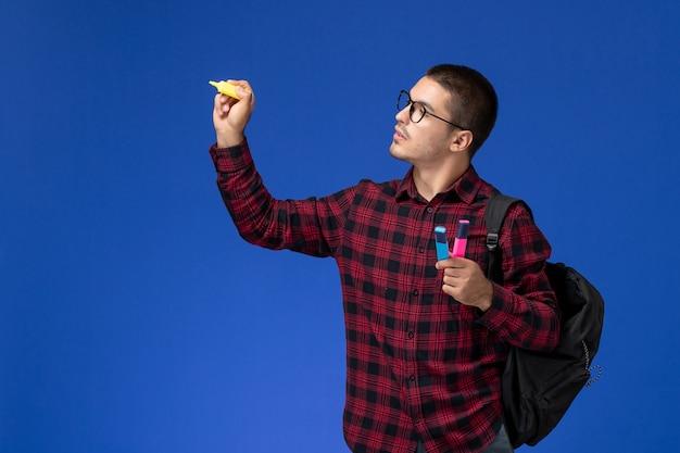 밝은 파란색 벽에 펠트 펜을 들고 배낭과 빨간색 체크 무늬 셔츠에 남성 학생의 전면보기
