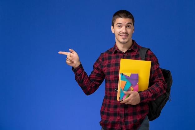 水色の壁にファイルとコピーブックを保持するバックパックと赤い市松模様のシャツの男子学生の正面図