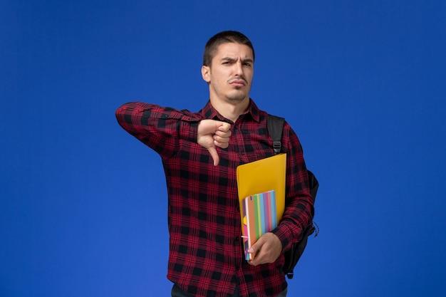 파란색 벽에 파일 및 카피 북을 들고 배낭과 빨간색 체크 무늬 셔츠에 남성 학생의 전면보기