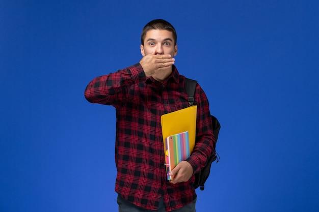 Вид спереди студента в красной клетчатой рубашке с рюкзаком, держащим файлы и тетради на синей стене