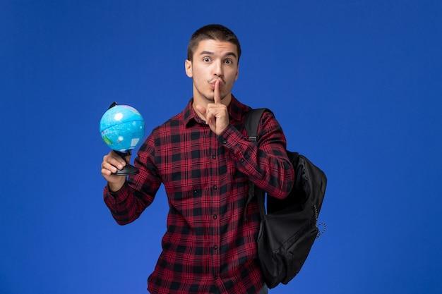 水色の壁に小さな地球儀を保持しているバックパックと赤い市松模様のシャツの男子学生の正面図
