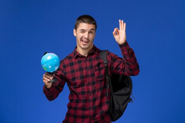 Вид спереди студента в красной клетчатой рубашке с рюкзаком, держащего маленький глобус на голубой стене