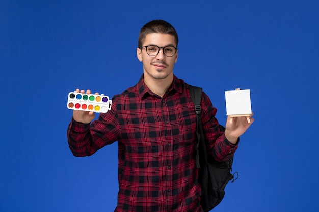 Вид спереди студента в красной клетчатой рубашке с рюкзаком с краской и мольбертом на синей стене