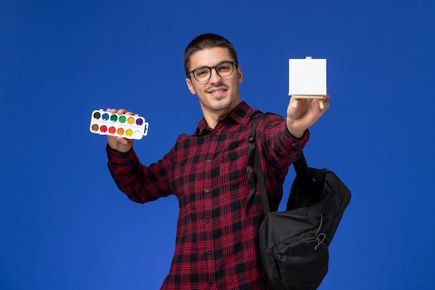 Вид спереди студента в красной клетчатой рубашке с рюкзаком, держащим краску и мольберт