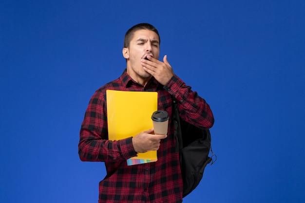 Вид спереди студента в красной клетчатой рубашке с рюкзаком, держащего желтые файлы и кофе, зевающего на синей стене