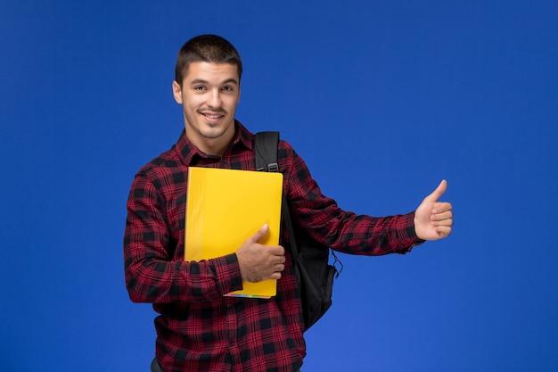 파란색 벽에 노란색 파일을 들고 배낭과 빨간색 체크 무늬 셔츠에 남성 학생의 전면보기