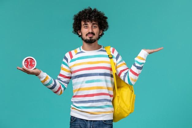 Студент в полосатой рубашке, одетый в желтый рюкзак, держит часы на синей стене, вид спереди