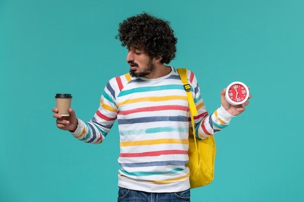 파란색 벽에 커피와 시계를 들고 노란색 배낭을 착용하는 스트라이프 셔츠에 남성 학생의 전면보기