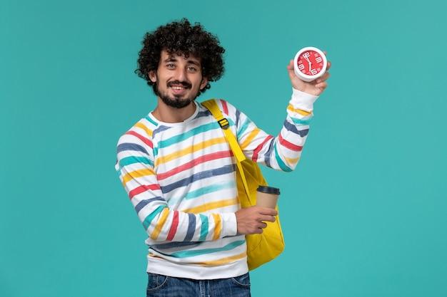 Студент в полосатой рубашке, одетый в желтый рюкзак, держит кофе и часы на синей стене, вид спереди