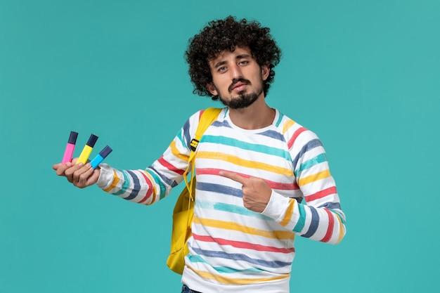 青い壁に色のフェルトペンを保持している黄色のバックパックを身に着けている縞模様のシャツの男子学生の正面図