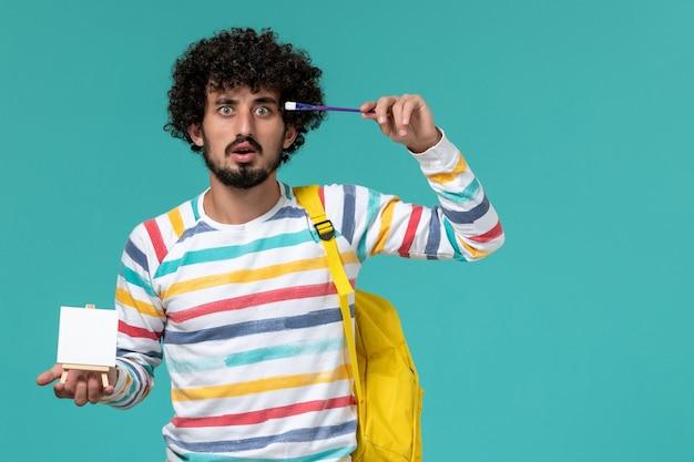 青い壁にイーゼルとタッセルを保持している黄色のバックパックを身に着けている縞模様のシャツの男子学生の正面図