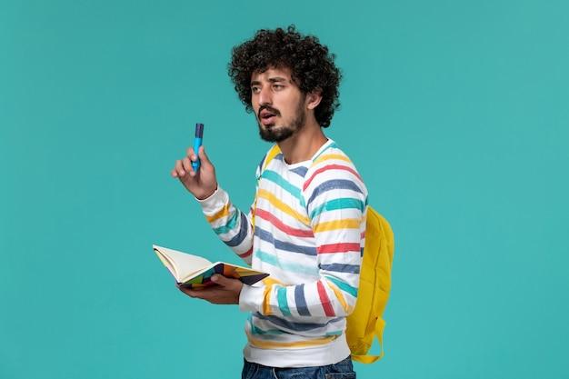 青い壁にフェルトペンとコピーブックを保持している黄色のバックパックを身に着けている縞模様のシャツの男子学生の正面図
