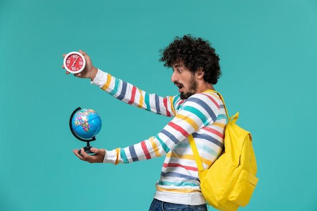 Студент в полосатой рубашке, одетый в желтый рюкзак, держит глобус и часы на синей стене, вид спереди