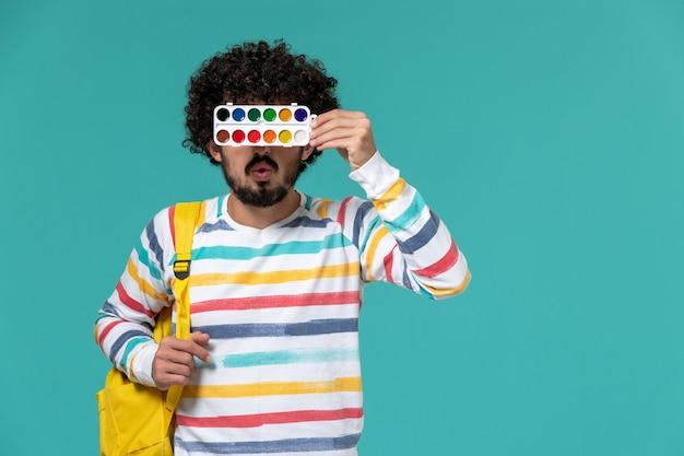 파란색 벽에 페인트를 들고 노란색 배낭을 입고 스트라이프 셔츠에 남성 학생의 전면보기