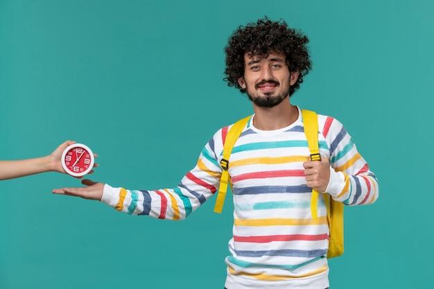 밝은 파란색 벽에 웃는 포즈 노란색 배낭을 입고 스트라이프 셔츠에 남성 학생의 전면보기