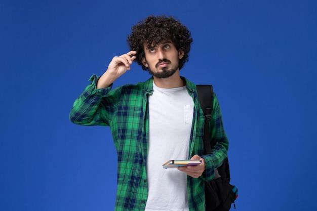 카피 북을 들고 파란색 벽에 생각하고 검은 배낭을 착용하는 남성 학생의 전면보기