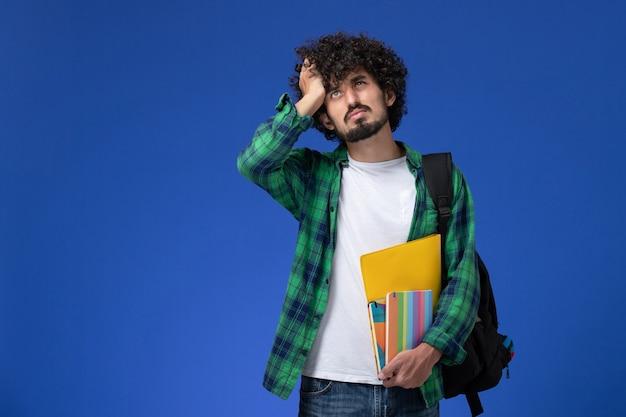 파란색 벽에 두통이있는 카피 북 및 파일을 들고 검은 배낭을 착용하는 남성 학생의 전면보기