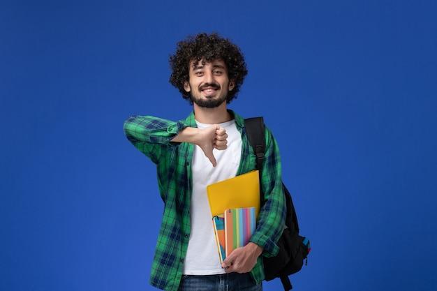 파란색 벽에 카피 북 및 파일을 들고 검은 배낭을 착용하는 남성 학생의 전면보기