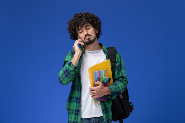 水色の壁に電話で話しているファイルとコピーブックを保持している黒いバックパックを身に着けている男子学生の正面図