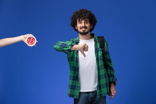 밝은 파란색 벽에 검은 가방을 입고 남성 학생의 전면보기