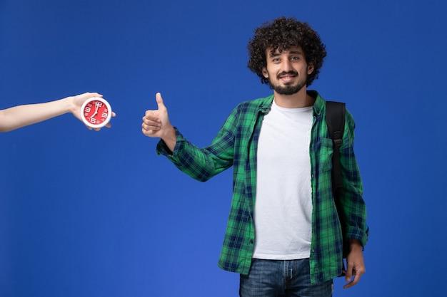 밝은 파란색 벽에 웃 고 검은 배낭을 입고 남성 학생의 전면보기