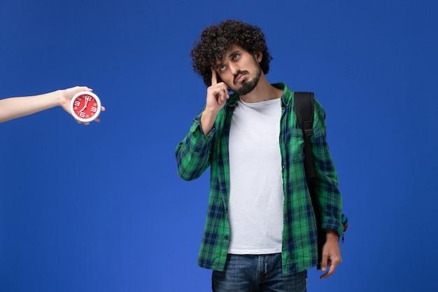 水色の壁を考えて黒いバックパックを身に着けている男子学生の正面図