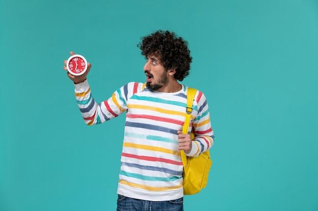 水色の壁に時計を保持している黄色のバックパックを身に着けている男子学生の正面図
