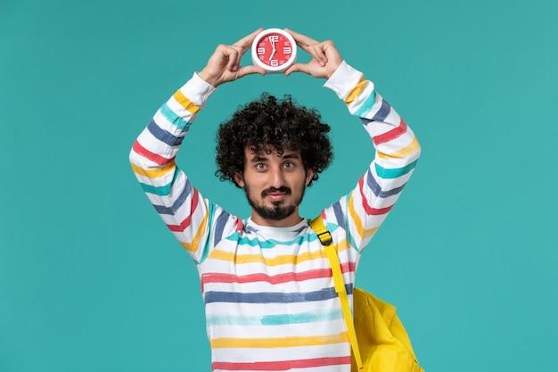 밝은 파란색 벽에 시계를 들고 노란색 배낭을 착용하는 남성 학생의 전면보기
