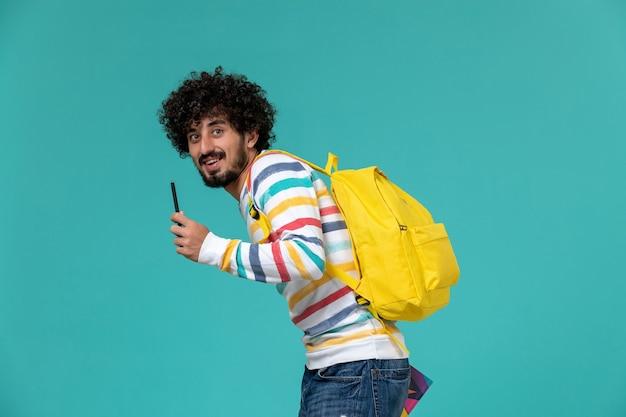 파란색 벽에 카피 북과 펜을 들고 노란색 배낭을 착용하는 남성 학생의 전면보기