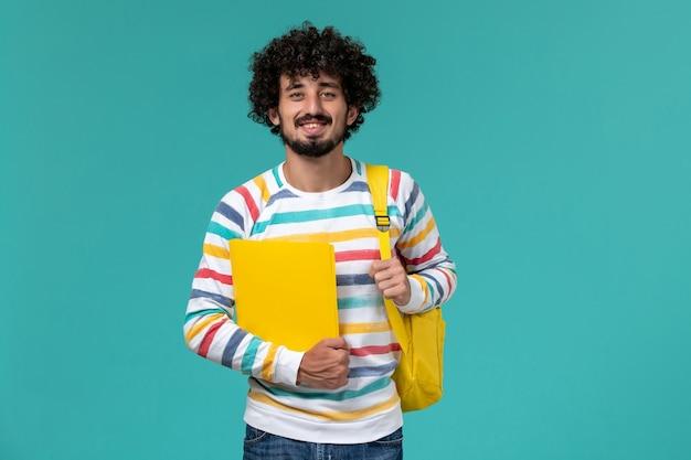 青い壁にファイルを保持している黄色のバックパックを身に着けている男子学生の正面図