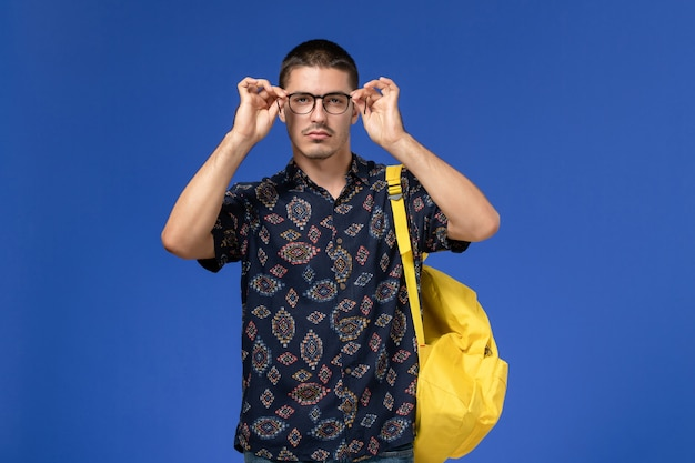 青い壁にポーズをとってカメラを見ている黄色のバックパックを身に着けている男子学生の正面図