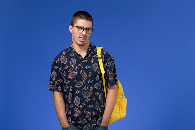 파란색 벽에 노란색 배낭 포즈를 입고 남성 학생의 전면보기