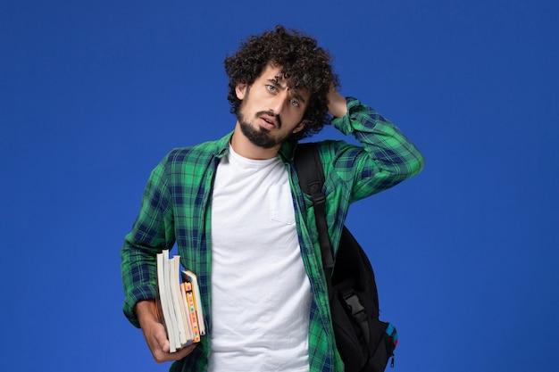 파란색 벽에 카피 북 및 파일을 들고 검은 배낭 남성 학생의 전면보기