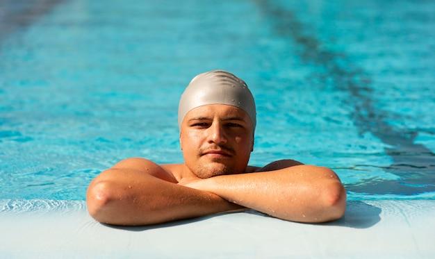 プールでポーズをとる男性スイマーの正面図