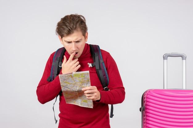 バックパックと白い壁の上の地図と男性観光客の正面図