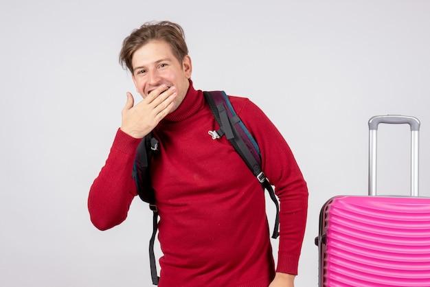 白い壁で笑っているバックパックと男性観光客の正面図