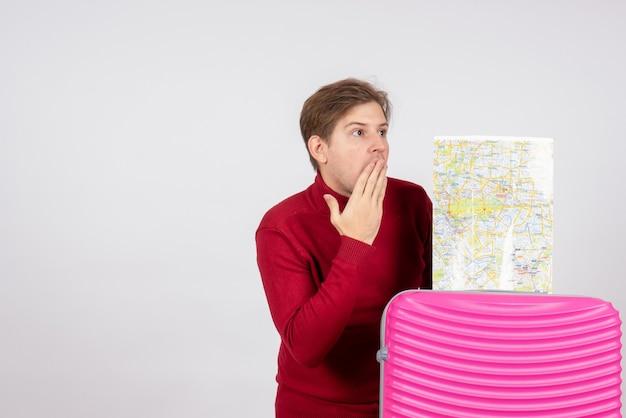 Вид спереди мужского туриста с картой и розовой сумкой на белой стене