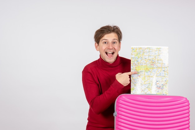 흰 벽에지도와 분홍색 가방 남성 관광객의 전면보기