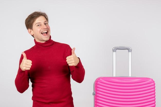 白い壁にピンクのバッグを持つ男性観光客の正面図