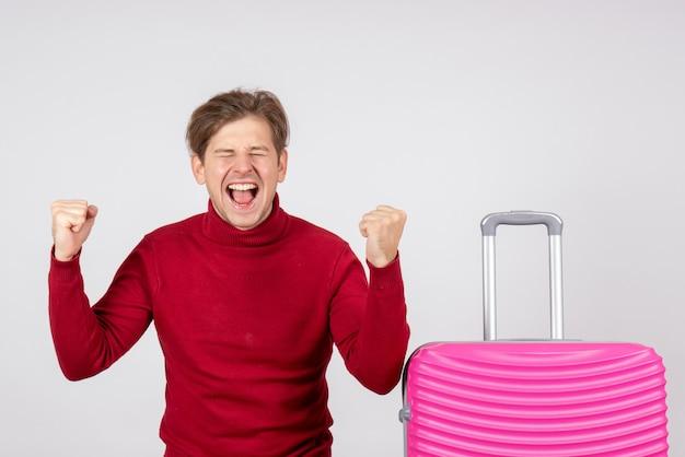 흰 벽에 분홍색 가방 남성 관광객의 전면보기