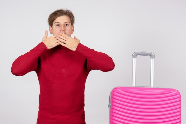 Вид спереди мужчины-туриста с розовой сумкой на белой стене
