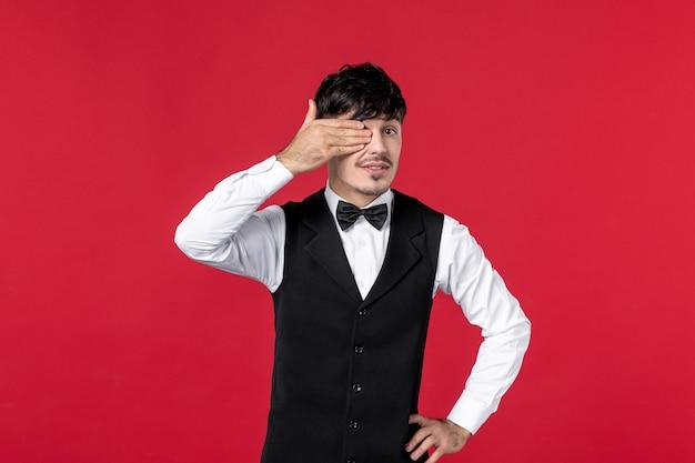 赤い背景の上の指で彼の顔の半分を閉じる首に蝶と制服を着た男性ウェイターの正面図